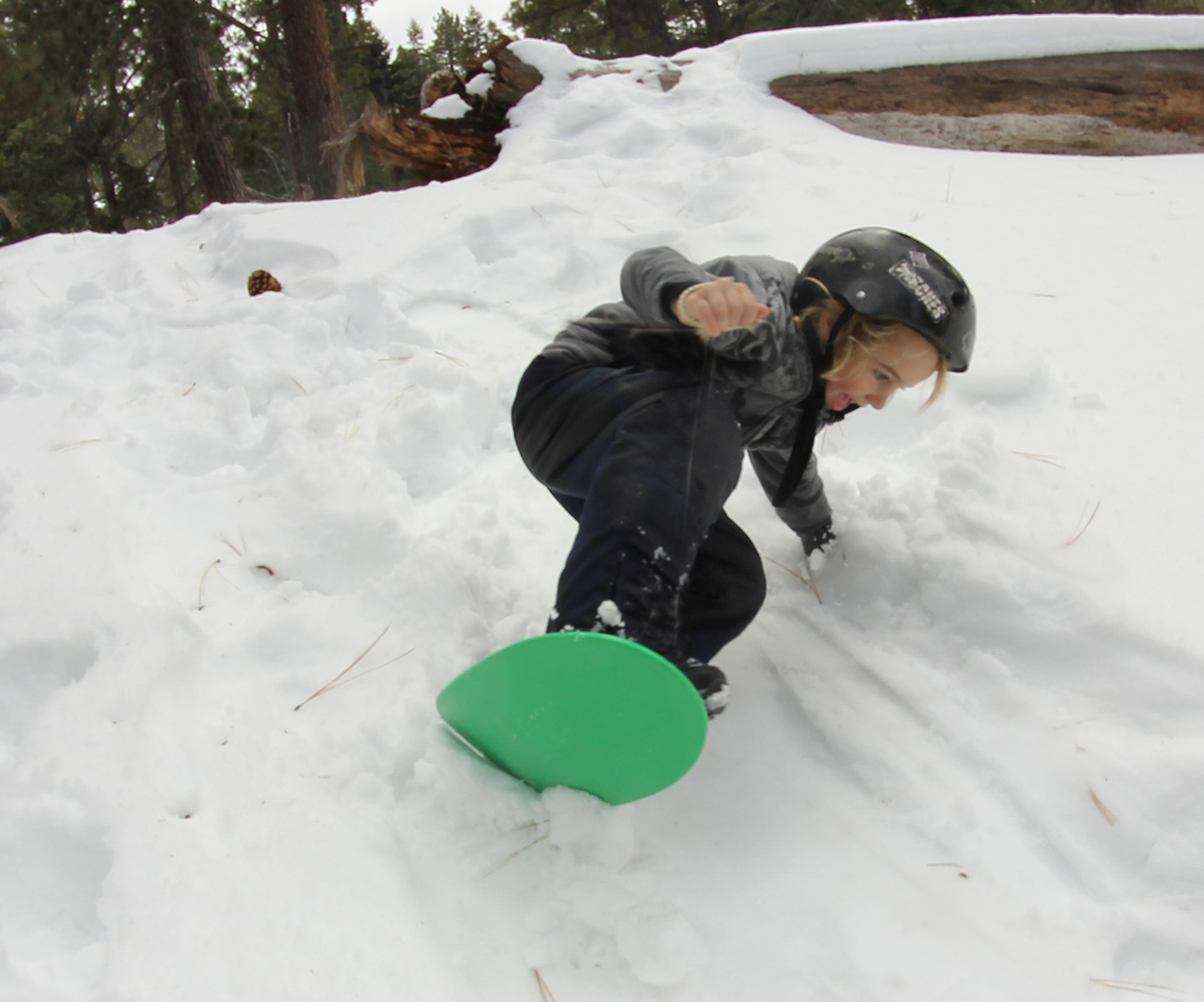 Kid boarding a Spooner in the snow